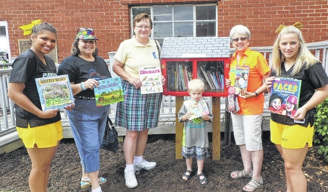 """The lively scene at this year's Bloomingburg Community Day included a lot of action at the bright red mailbox housing the Little Free Library sponsored by Altrusa International of Washington C.H. At times, entire families had children there sorting through books, thanks to coordinator Jeannie Bihl's roaming the grounds with a tote bag and handing out """"free samples."""" Miami Trace cheerleaders were just across the sidewalk painting faces, which also brought many children to that area of the town hall grounds. Shown are (from left) MT cheerleader Madison Perry, Altrusans Alice Craig and Lauran Perrill, Garrett Bihl, Altrusa's Literacy Committee member & Little Free Library coordinator Jeannie Bihl, and MT cheerleader Abbie Ellison."""