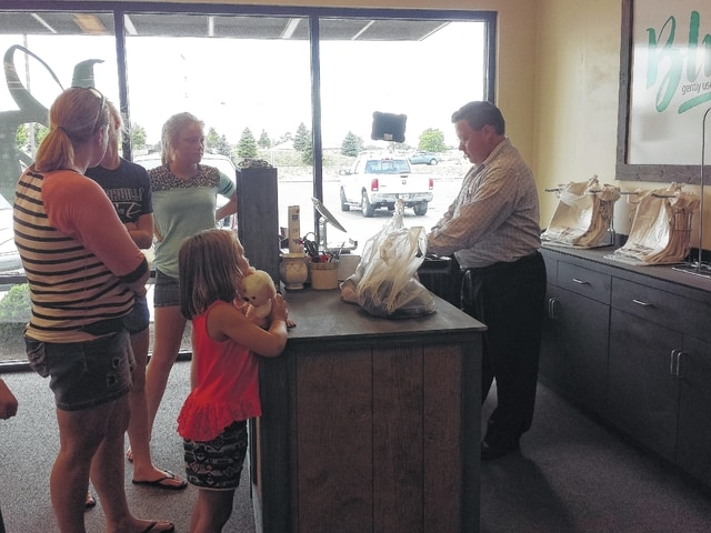 """Michael Cole, keyholder at """"Blue,"""" cashes out the last customers of the day on Friday evening. The inside of the business has changed and now includes a dressing room and a wood-style interior."""