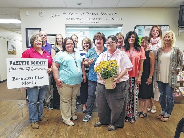 Vicki Congrove (center), clinic director, accepts flowers from Fayette County Chamber of Commerce Ambassadors and board members as Scioto Paint Valley Mental Health Clinic was named the September Business of the Month. Congrove is surrounded by SPVMH Center staff and Chamber Ambassadors and board members.