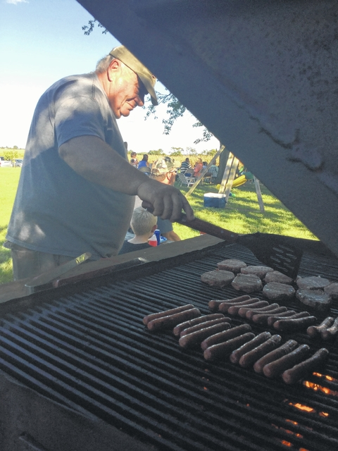 Jerry Crawford cooks up all-beef hot dogs and burgers for a large crowd Sunday's picnic.