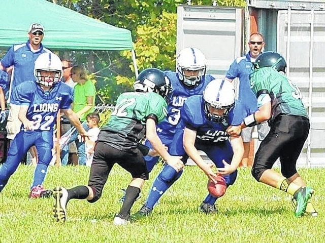 The Washington Blue Lion youth football team (grades 5 and 6) played at Fayetteville Saturday, Sept. 24, 2016. Washington won the game, 6-0. Above, Reece Self (56) recovers a fumble for Washington. At left is Corey Kennedy (32).