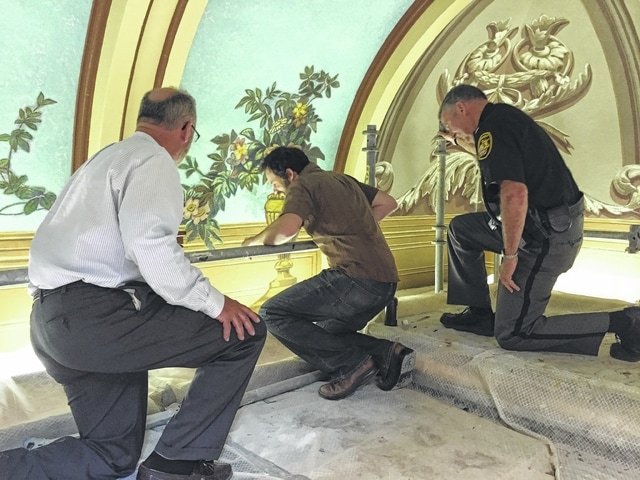 Judge Beathard (left) and a Fayette County deputy sheriff (right) look at the progress made by MuralWorks in restoring the decorative paintings in the courthouse.