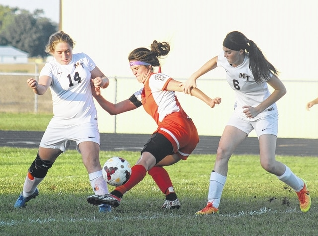 Miami Trace's Aubrey Schwartz (left) and Hanna Reisinger (at right) teamed up to apply defensive pressure to a Wilmington player during an SCOL match at Miami Trace High School Thursday, Sept. 22, 2016.