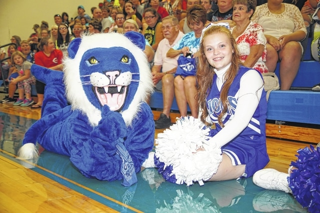 Washington High School cheerleader Brooklyn Stanley is pictured with the Blue Lion mascot during the pep rally held at the school on Wednesday evening.