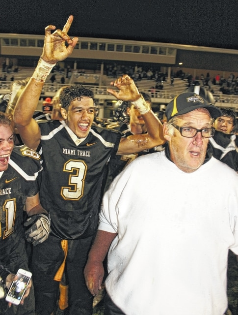 Miami Trace head coach Steve Bartlett, at right, celebrates a 33-6 victory over the McClain Tigers Friday night. The win was Bartlett's 200th coaching victory. Also pictured are DeAndre Pettiford (3) and Quetin Harper (81).