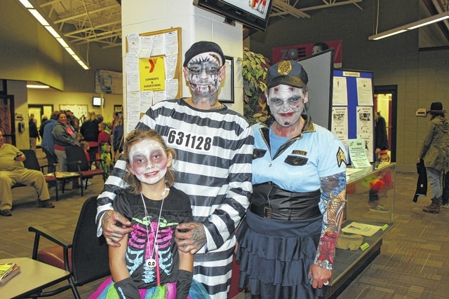 The annual Beggar's Night Boonanza, sponsored by the Record-Herald and hosted by the Fayette Family YMCA, was held Thursday evening with a large crowd attending. Pictured are Trinity Brown, Roger Stevens and Nicole Brown with their undead-themed costumes.