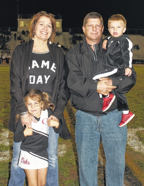 Jeff Conroy is joined by wife Rogina, grandson Baylor (whom he is holding) and granddaughter Bentley, during a halftime recognition ceremony at the Miami Trace-McClain game Friday, Sept. 30, 2016. The former Miami Trace head coach will be inducted into the Ohio High School Football Coaches Association Hall of Fame in June, 2017.