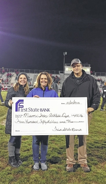 From left to right, Ellie Zint and Karen Cassidy of First State Bank recently made a donation presentation to Miami Trace Athletic Director Aaron Hammond.