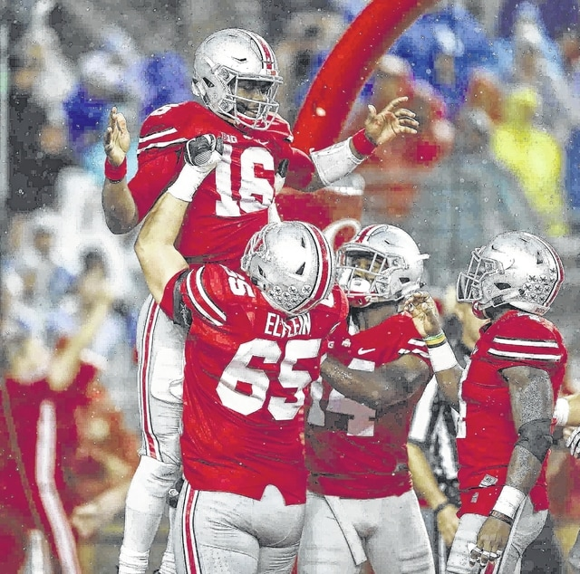 Ohio State center Pat Elflein (65), one of two first-team All-Americans on OSU's offensive line, and quarterback J.T. Barrett celebrate a touchdown run by Barrett.