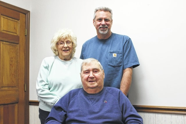 Roger Stockwell (seated) is pictured with his wife Becky and son Kevin during his interview at the Record-Herald Thursday. After dealing with a life-threatening disease, Stockwell was able to return to help with the family farm by harvesting a bit of corn. His beloved passion of agriculture has led to a full family who continues to support each other no matter what.