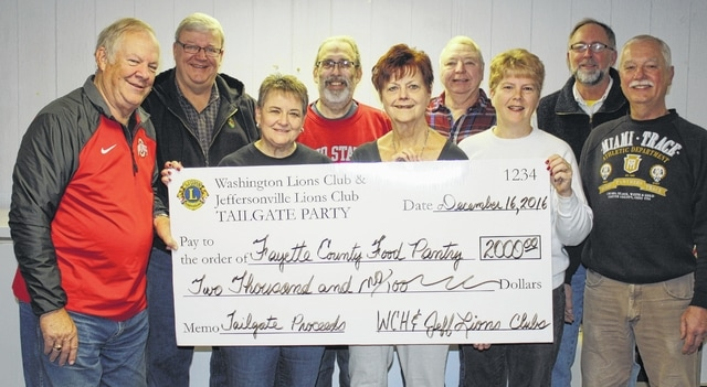 Representatives of the Fayette County Food Pantry accepted the check of $2,000 presented by the Jeffersonville and Washington C.H. Lions from the proceeds of the Beat Michigan Tailgate Party. Pictured in the first row are WCH Lion Jay Carey; food pantry volunteers Norma Kirby, Karen Bloedel, and Sue Willis (also a WCH Lion); and Lion Bob Mowrey (WCH). Second row: Lions Dan Dean (WCH), Chris Bowshier (WCH), Jerry Spahr (Jeff) and Bruce Willis (WCH).