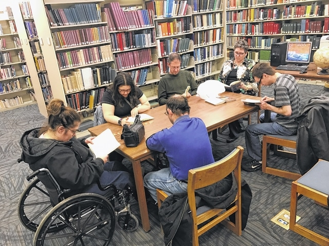 Fayette County's Next Chapter Book Club is pictured reading aloud at the library.