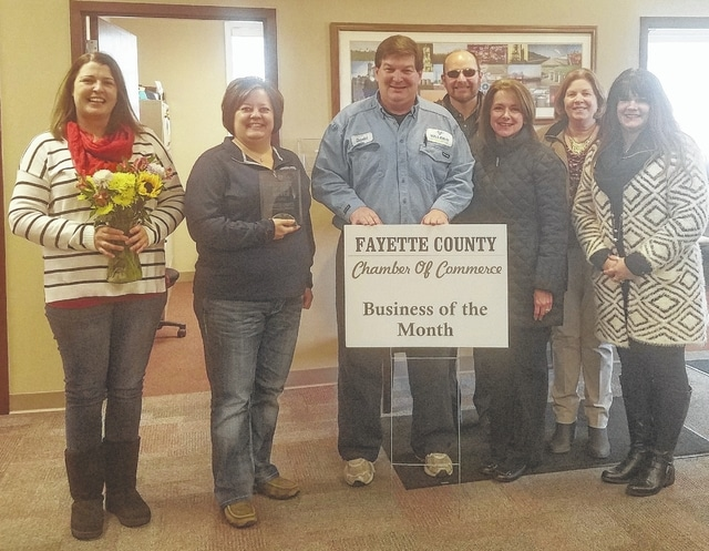 Valero plant manager Karl Charron (center) accepts the Business of the Month sign from chamber president Whitney Gentry (left) and the Chamber Ambassador Team.