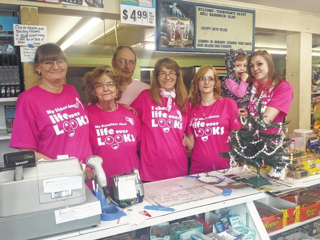"""Owners, employees and family met at Thompson's Depot in Washington Court House Wednesday to celebrate the life of Becky Lankford, an employee at Thompson's Depot. Lankford was diagnosed and treated for breast cancer in December. She expressed an urgency for everyone to get checked and treated as soon as possible. She decided, after a bit of encouragement from loved ones, to keep her """"life above her looks"""" and received a mastectomy as treatment. Now her loved ones wear this shirt in support. Charms can be purchased at Thompson's for $1 and will support Lankford. Pictured (L to R): Regina Lankford, Ruthann Thompson, Mike Thompson, Becky Lankford, Amanda Sanders and Tesla Brown holding Bradlee Lankford."""