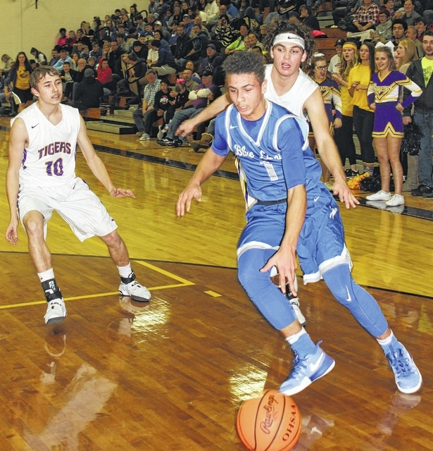 Washington sophomore Dillon Steward drives toward the basket during an SCOL game at McClain High School in Greenfield Friday, Jan. 27, 2017. Pictured for McClain are (l-r); Dakotah Duncan and Dalton Mischal.