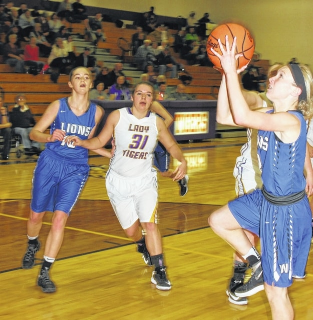 Washington junior Maddy Garrison takes the ball to the basket during an SCOL game at McClain High School in Greenfield Wednesday, Jan. 18, 2017. At left are Washington senior Savannah Wallace and McClain sophomore Liz Kegley.