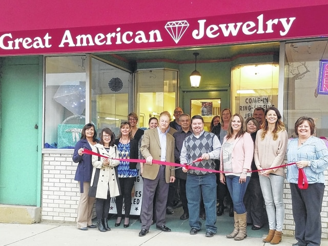 Members of the Chamber Ambassador team and representatives from the City of Washington gather around the Great American Jewelry staff while owner Shane Johnson (center) cuts the ribbon with staff members Steve Shiltz (left) and Misti Roese (right).