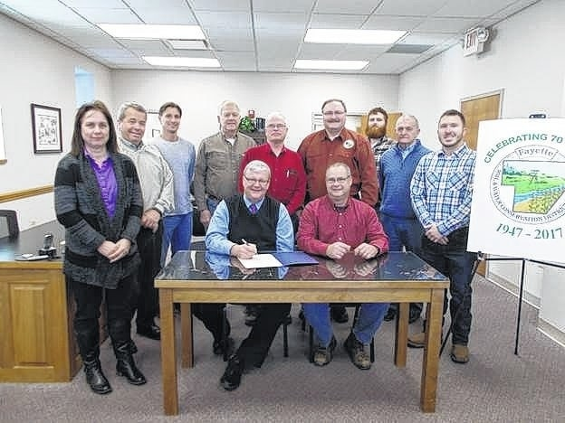 Fayette County Commissioner Dan Dean signs a proclamation in honor of the 70th anniversary of Fayette Soil & Water Conservation District. Front Row: commissioner Dan Dean, supervisor Fred Melvin; Back Row: Natural Resource Specialist Brigitte Hisey, commissioner Tony Anderson, supervisors Richard Davidson, Gary Reiterman, Jim Garland, director Chet Murphy, district technician Malcolm Miller, commissioner Jack DeWeese, and supervisor Kyle Montgomery.