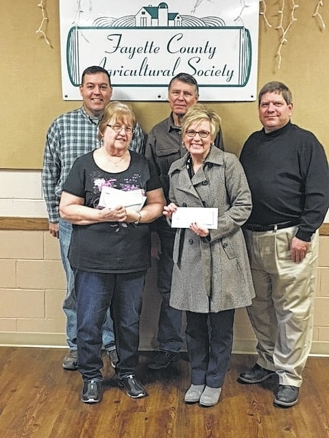 The winners for the Fayette County Agricultural Society raffle were picked Saturday evening. Pictured here (front row) are winners Maggie Overstake, who won the $20,000 grand prize, and Melanie Cockerill, who won the $5,000 second prize. Pictured with them (back row) are Ag Society Directors Michael Carson, Wayne Arnold and Doug Marine. The drawing was held at the Smokin Ham Dance Saturday, Feb. 11.