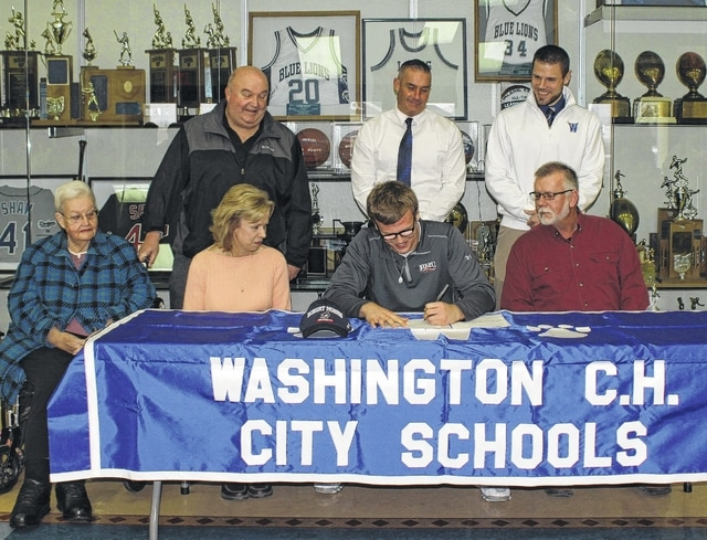 Trevor Hicks, Washington High School senior, signs a letter of intent to attend Robert Morris University (in Pittsburgh) Wednesday morning. In front, (l-r); Barbara Dean, Hicks' grandmother; mom Dinah, Hicks and his dad, Roger, and in back, l-r); his uncle, Tom Dean, Blue Lion head football coach Chuck Williamson and athletic director, Jon Creamer.