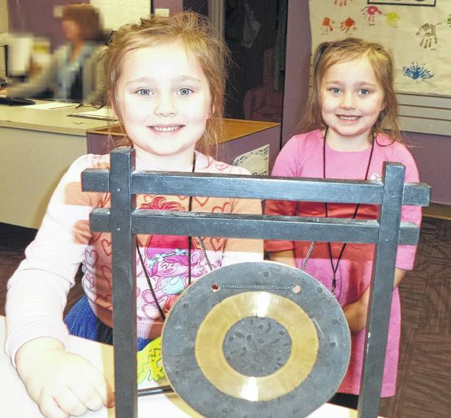 Several children have obtained their library cards this month at Carnegie Public Library. Brynlynn and Catelynn ring the gong after getting their cards.