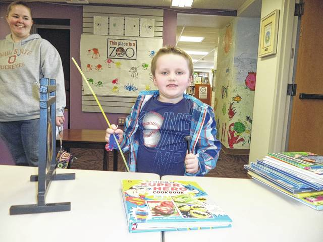 Several children have obtained their library cards this month at Carnegie Public Library. Caleb is pleased with his book and his prizes.