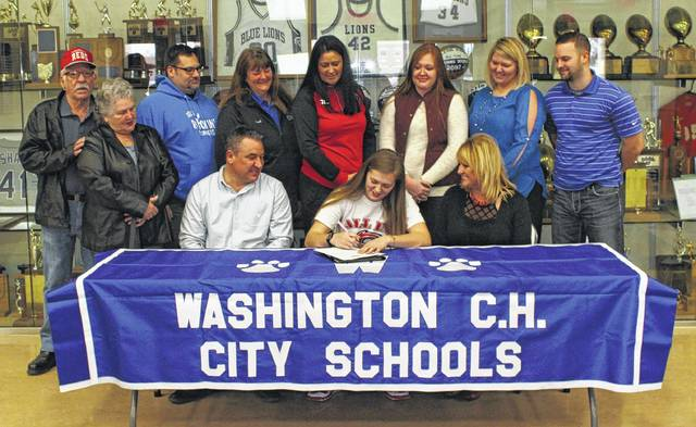 Washington High School senior Victoria Jones, seated, middle, signs a letter of intent to attend Rio Grande University where she will continue her education and be a member of the volleyball team. She is flanked by her parents, Fred and Laura Jones and joined by (standing, l-r); her grandfather and grandmother, Fred and Barb Jones, former high school coach John Buyer, club coach Ruth Ernst, Rio Grande women's volleyball coach Billina Donaldson, her sister, Elizabeth Jones, current Washington High School volleyball coach Ashley DeAtley and current assistant volleyball coach at WHS, Zach Balahtsis.