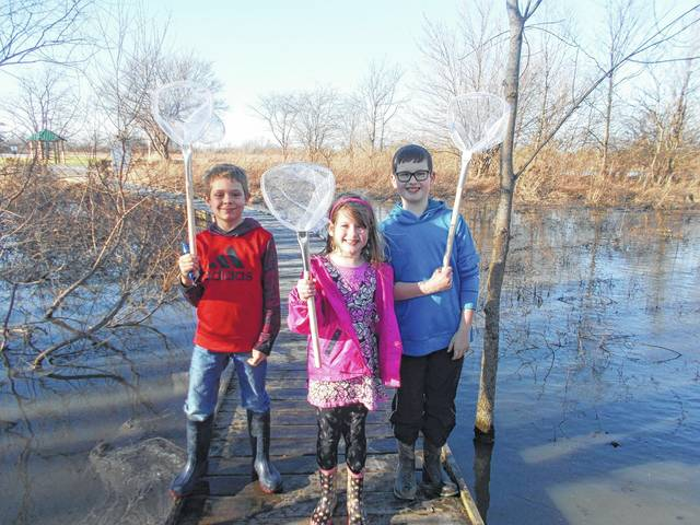 Logan Helfrich, and Annabel and Owen Teter search for frogs and toads.