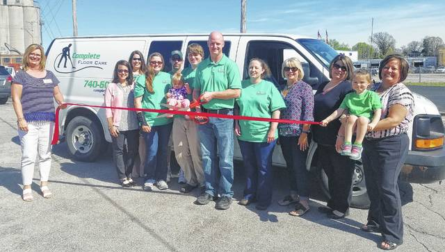 Owner Todd Jackson (center) and the Complete Floor Care team announce the opening of their business with some help from the Chamber of Commerce.