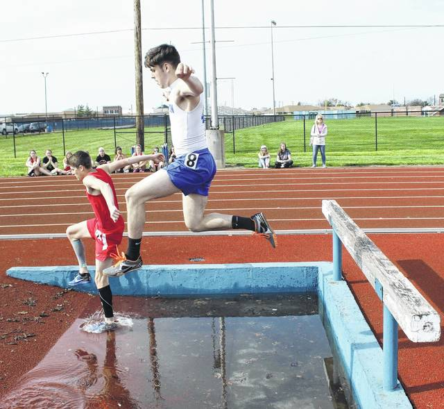 Chris Conger leaps the water hazzard during the 2000-meter steeplechase Friday, April 14, 2017.