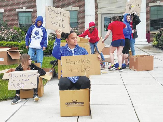 "Jaelyn Mason and several other Washington High School Hi-Y members were ""Homeless for a Day"" to help raise money for The Well at Sunnyside Thursday in front of the high school. They used leftover cardboard to build places to sit and signs to encourage drivers to donate."