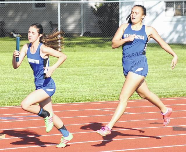 Washington's Jerrica Hites takes off on her leg of the 4 x 200-meter relay, having made the exchange with Jaelyn at the Division II District track meet Tuesday, May 16, 2017 at Washington High School.