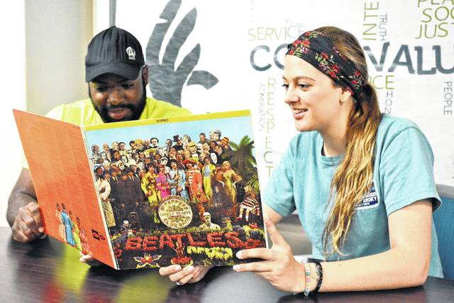 Wilmington College senior David Henry and sophomore Jennifer Cochran look over a relic from the 1960s, a copy of the Beatles' landmark album, Sgt. Pepper's Lonely Hearts Club Band.