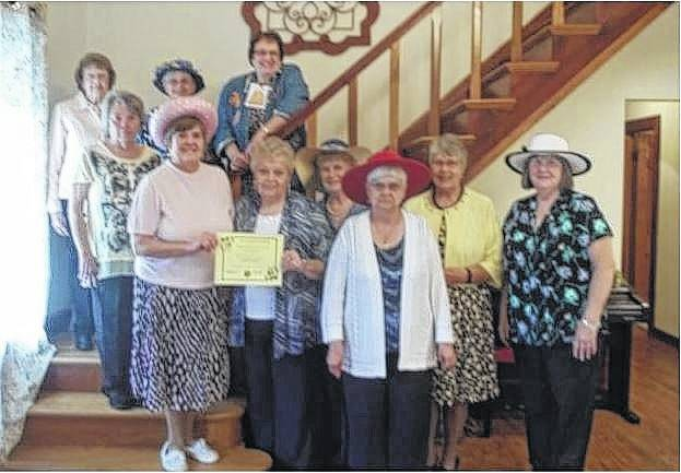 Fayette Garden Club President Pam Rhoads accepts a certificate from Ohio Association of Garden Clubs Region 16 Director Linda Morgan. Next is Jodi Kirk, Connie Swayne, Pat Parsons, and Debbie Carr. Behind on the steps are Marge Clifford, Joanne Montgomery, Jean Smith and Linda Warfield.