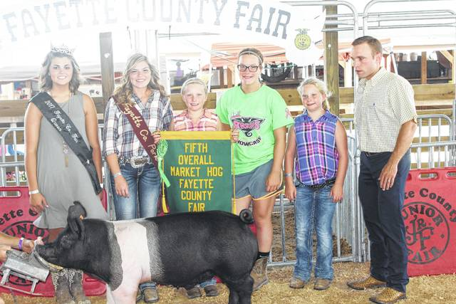 Carley Payton (holding the banner) finished fifth overall at Wednesday's Fayette County Junior Fair Swine Show. She is pictured with family and fair royalty.