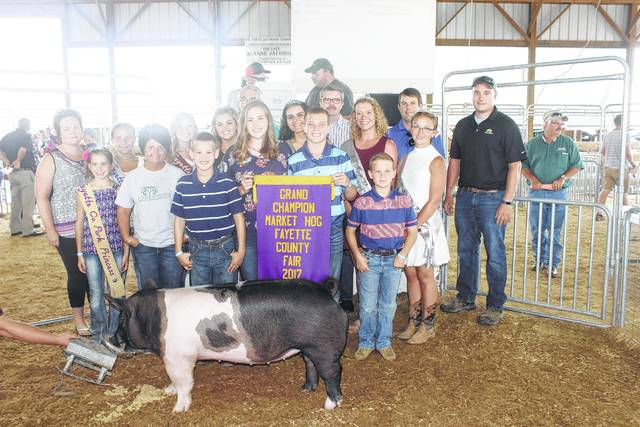 Graham Carson's grand champion hog sold for $2,500 at the Fayette County Fair Hog Sale on Thursday evening. Carson is pictured with buyers, family and fair royalty: (front row) Pork Princess Emily Reeves, Jodi Yengar of 4 Seasons, Garrett Carson, Meri Grace Carson, Gabriel Carson, (back row) Tracy Foy of Bluegrass Farms, Pork Princess Shelby Mayer, Pork Queen Kendal May, Fair Queen Marissa Sheets, Fair Attendant Susanna Eckstein, Fair Attendant Clare Sollars, Fair Attendant Skylynn Barden, Dick Carson of Shady Grove Campgrounds, Keith Tooill of McDonald's, Ryan Garrison of Melvin Stone Company, and Adam Schmerge of Co-Alliance.