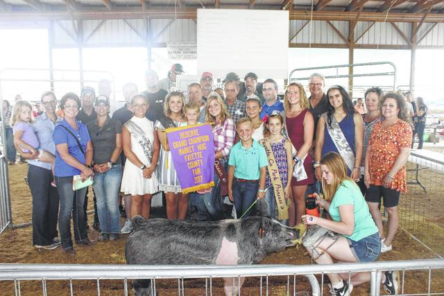 Kaden Bryant's reserve champion hog sold for $2,400 at the Fayette County Fair Hog Sale on Thursday evening. Bryant is pictured with buyers, family and fair royalty: (front row) Sarah and Paisley Thompson, Sheila Johnson of Kroger, Jenny Coe, Fair Attendant Skylynn Barden, Fair Queen Marissa Sheets, Ella Bryant, Pork Queen Kendal May, Pork Princess Shelby Mayer, Pork Princess Emily Reeves, Fair Attendant Clare Sollars, Fair Attendant Susanna Eckstein, Diane Faris Munro of Faris Insurance, (second row) Josh Hagler of Seed Consultants, Jeff Litteral of Sugarcreek Packing, John Gruber, Doug Shannon of Merchants Bank, Fayette County Commissioner Dan Dean, Tracy Foy of Bluegrass Farms, (back row) Mark Richards of First State Bank, Corey Farrens of Farrens Ag Service, Brad Reisinger of Bane Welker, and Cody Kirkpatrick of JD Equipment.