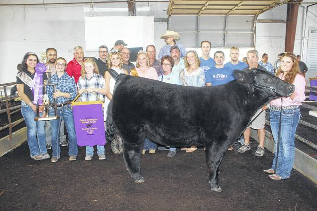 McKenzie Riley's grand champion beef steer sold for $5,000 at the Fayette County Fair Beef Steer Sale on Friday evening. Riley is pictured with buyers, family and fair royalty: (first row) Fair Attendant Susanna Eckstein, Macie Riley, Gracelyn Zimmerman, Fair Queen Marissa Sheets, Beef Queen Lindsey Worley, Sheila Johnson of Kroger, Fair Attendant Clare Sollars, Devin Bilski of Congressman Steve Stivers' office, Fayette County Commissioner Tony Anderson, (back row) Fayette County Prosecutor Jess Weade, Shane McMahon of McMahon Insurance, Keith Tooill of McDonald's of Fayette County, Buck Minyo of LCNB, Jim Gusweiler of Gusweiler, Travis Mick of Prime Meats, Adam Rapien and Chase Enochs of Congressman Steve Stivers' office.