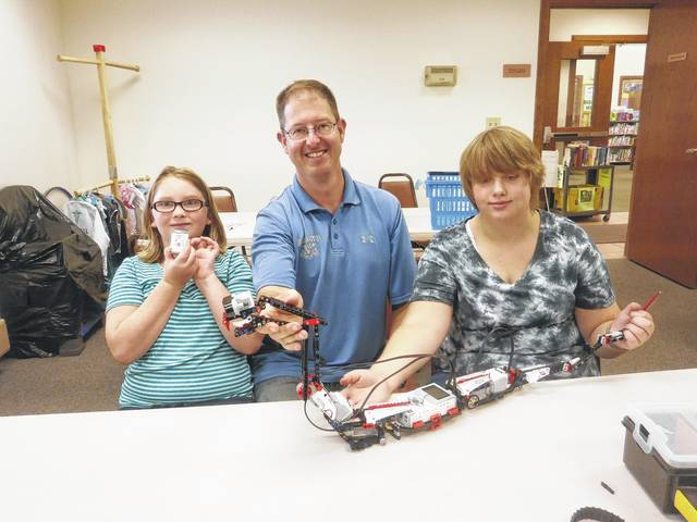 Jeffersonville Branch Library was the place to be for Aaron's STEM program: Building a R3PTAR from a specialty LEGO set. Shown here in the picture are Lilly, Aaron and Holly with their creation: the R3PTAR.