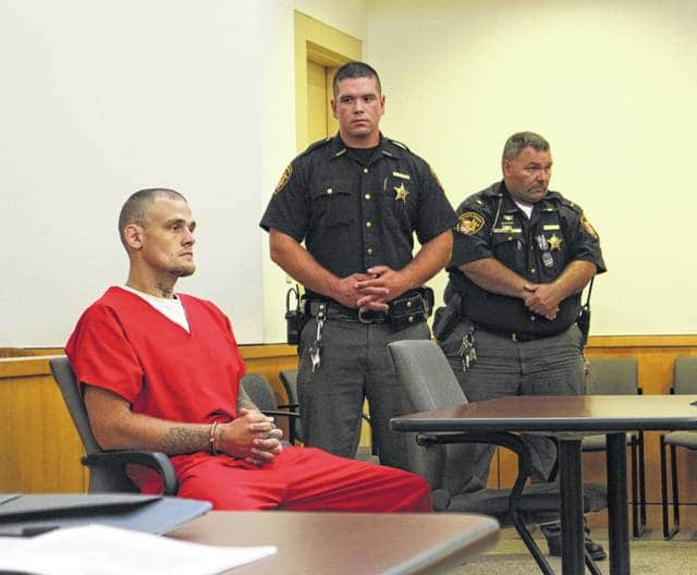 Jeffrey Ryan Holsinger, left, sits in court Friday afternoon guarded by two deputies with the Highland County Sheriff's Office.