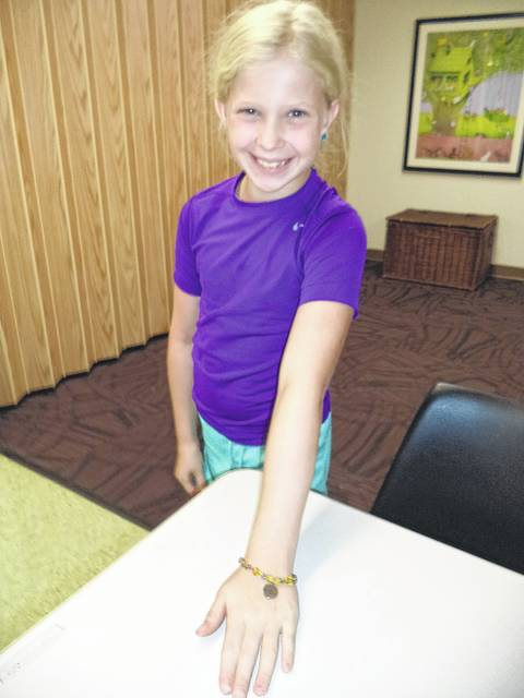 Nora Morrison displaying her bracelet made during a beading class.