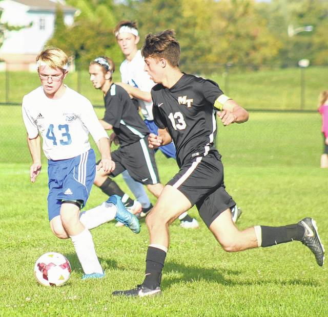 Miami Trace's Brett Lewis, right, advances the ball against the defensive pressure of Washington's Allan Schreckengaust (43) in a Frontier Athletic Conference match at Washington High School Tuesday, Sept. 19, 2017. Also pictured, for Miami Trace is Ethan Powell and for Washington, Jordan Behm.