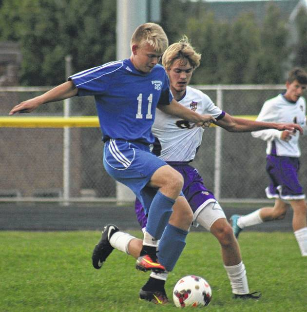 Washington Blue Lion senior Jack Luebbe advances the ball while pressured by a McClain defender during a Frontier Athletic Conference match at McClain High School in Greenfield Thursday, Sept. 14, 2017.