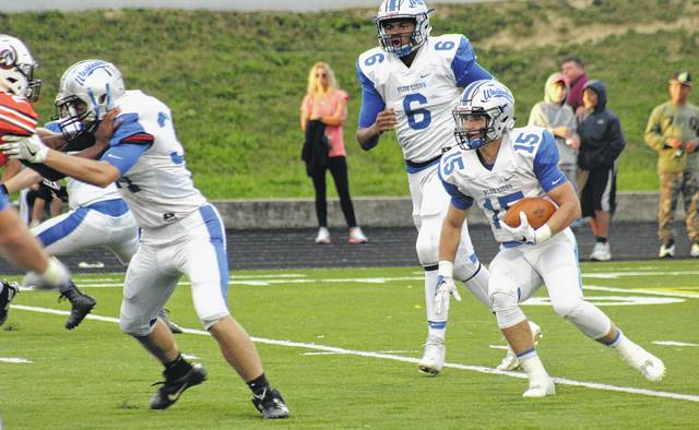 Jacob Rice (15) carries for the Blue Lions during a non-conference game at Delaware Hayes High School Friday, Sept. 15, 2017. Also pictured is quarterback Richie Burns (6) and Jameson McCane (at left), blocking for Rice.