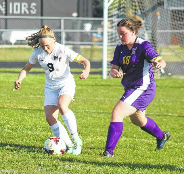 Miami Trace senior Jillian Sollars (left) maintains possession of the ball against a defender from McClain during a Frontier Athletic Conference match at Miami Trace High School Tuesday, Sept. 26, 2017.