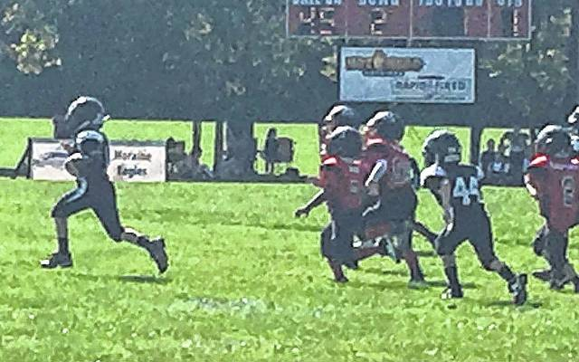 Gabe Carson (at left) for the Miami Trace third grade White team scampers for a 56-yard touchdown against West Carrolton on Saturday, Sept. 16, 2017. Also pictured is Joenus Eakins (44) at right.