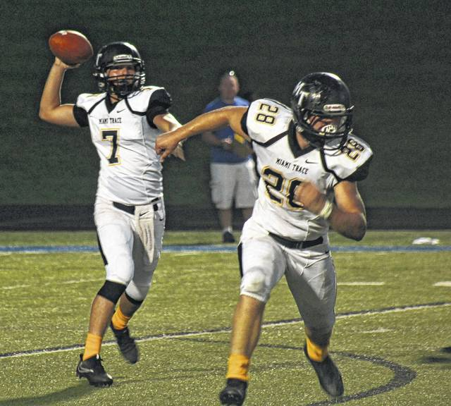 Miami Trace junior quarterback Tyler Taylor drops back to pass while Josh Liff (28) watches for a player to block during a non-conference game at Zanesville Friday, Sept. 22, 2017.