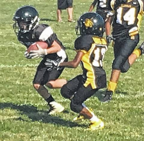 Corbin Melvin catches a pass from Ben Mathews for a first down this past Saturday, Sept. 23, 2017, against Meadowdale for the Miami Trace 6th grade Black squad.