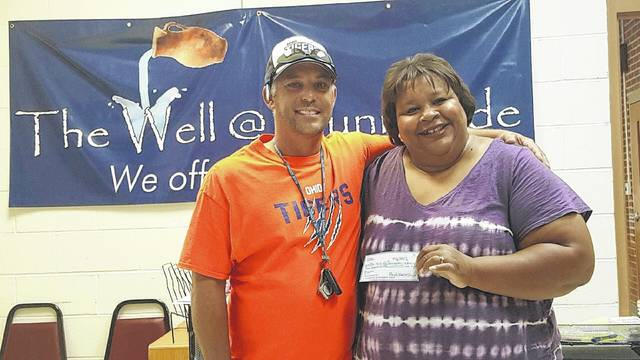 The Ohio Tigers Softball program donated about $200 to The Well at Sunnyside after a 5K held in August. This was one of several fund raising efforts by Boyd Kearns (left), including the upcoming Classic Car and Bike Show on Sunday, where members of the WCH Cougars will help. He is pictured with Chiquita Nash, free store director and volunteer coordinator with The Well.