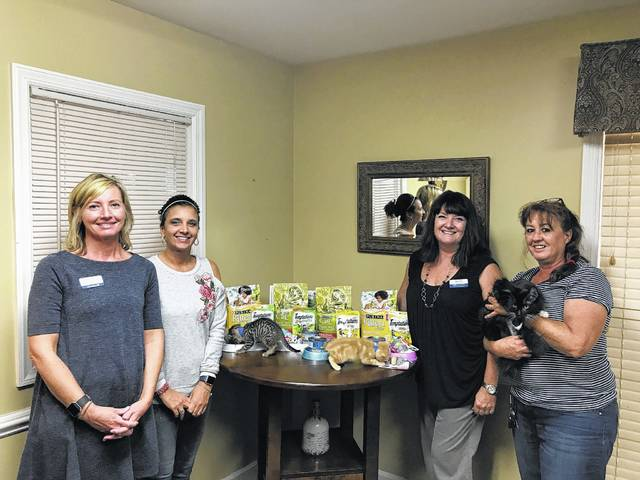 "Carriage Court Assisted Living recently hosted a pet adoption to go along with the ""Family is Forever"" theme for National Assisted Living Week. Pictured from left to right are Holly Cottrill of Heartland Hospice, Valerie Campbell, activities director with Carriage Court, Beth McCane, director of sales and marketing with Carriage Court and Cindy Zindorf, assistant adoption coordinator with the Fayette Humane Society. Also pictured are Solar, Flame and Moon who are all available for adoption at the Fayette Humane Society."